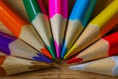 Lápices multicolores que forman un semi-círculo del color aislado en fondo de madera imagen de archivo libre de regalías