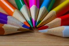 Lápices multicolores que forman un semi-círculo del color aislado en fondo de madera imágenes de archivo libres de regalías