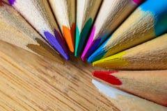 Lápices multicolores que forman un semi-círculo del color aislado en fondo de madera fotos de archivo libres de regalías