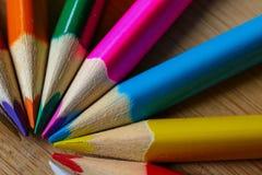 Lápices multicolores que forman un semi-círculo del color aislado en fondo de madera imagen de archivo