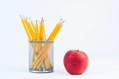 Lápices para la escuela y una manzana roja Imagen de archivo