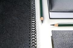 Lápices verdes entre los cuadernos Imágenes de archivo libres de regalías