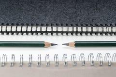 Lápices verdes entre los cuadernos Imagen de archivo