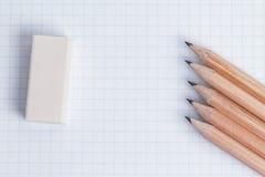 Lápices y borrador en la página del cuaderno Imágenes de archivo libres de regalías