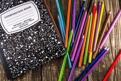 Lápices y cuaderno coloreados de la composición imágenes de archivo libres de regalías