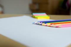 Lápices y etiquetas engomadas coloreados en una hoja blanca Imagen de archivo libre de regalías