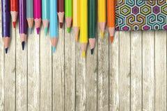 Lápices y libro coloreados en la tabla imágenes de archivo libres de regalías