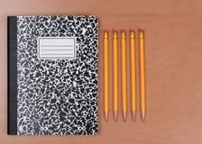 Lápices y libro del tema Foto de archivo libre de regalías