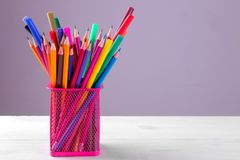 Lápices y marcadores multicolores en un vidrio para los lápices en un fondo gris Imagen de archivo