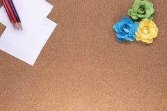 Lápices y papel con las rosas de papel Imagen de archivo