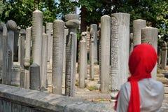 Lápida mortuaria vieja islámica en un cementerio y mujeres Fotografía de archivo