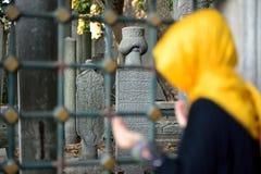 Lápida mortuaria vieja islámica en un cementerio y mujeres Fotos de archivo