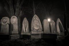 Lápidas mortuorias en la noche Fotos de archivo libres de regalías