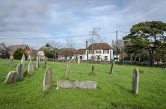 Lápidas mortuorias en un cementerio con el Pub del pueblo en el fondo Imágenes de archivo libres de regalías