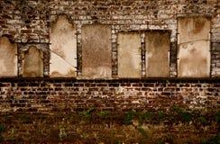 Lápidas mortuorias en una pared de ladrillo Imágenes de archivo libres de regalías