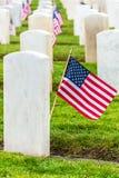 Lápidas mortuorias militares de los veteranos y banderas americanas Imagenes de archivo