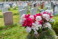 Lápides em um cemitério na queda com flores Imagem de Stock