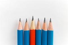 Lápis afiados simples isolados no fundo branco, vermelho entre o azul Imagem de Stock