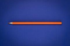 Lápis alaranjado no papel azul Fotografia de Stock