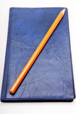 Lápis amarelo em um diário azul Imagem de Stock Royalty Free