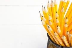 lápis amarelos no vidro preto em um fundo branco Fotos de Stock Royalty Free