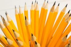 lápis amarelos no vidro preto em um fundo branco Foto de Stock Royalty Free