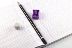 Lápis, apontador, eliminador, livro imagens de stock