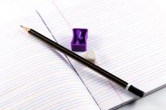 Lápis, apontador, eliminador, livro imagem de stock