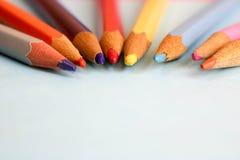Lápis apontando coloridos de madeira coloridos brilhantes bonitos para tirar Espaço liso da configuração e da cópia no fundo azul imagem de stock