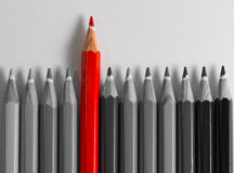 Lápis cinzento em ordem com o um vermelho que está para fora imagens de stock royalty free