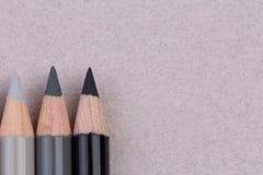 Lápis cinzentos e pretos na textura de papel pastel bege do grunge da grão grosseira imagens de stock royalty free