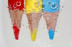 Lápis colorido sob a água imagem de stock