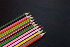 Lápis coloridos ajustados no fundo de madeira preto, Imagem de Stock