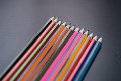 Lápis coloridos ajustados no fundo de madeira preto, Foto de Stock