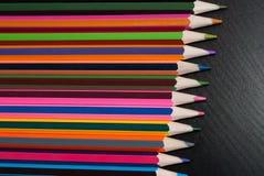 Lápis coloridos ajustados no fundo de madeira preto, Fotografia de Stock