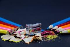 Lápis coloridos apontados contra lápis sem corte com apontador metálico e aparas coloridos do lápis no preto Foto de Stock Royalty Free