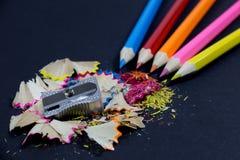 Lápis coloridos apontados que vêm do canto, do apontador metálico e dos aparas coloridos do lápis no preto Imagens de Stock
