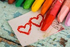 Lápis coloridos brilhantes em um fundo de madeira velho do verde azul Dois corações vermelhos pintados em uma fatia de papel Fotos de Stock