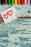 Lápis coloridos brilhantes em um fundo de madeira velho do verde azul Dois corações vermelhos pintados em uma fatia de papel Foto de Stock