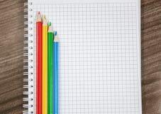 Lápis coloridos colocados no caderno branco Imagem de Stock