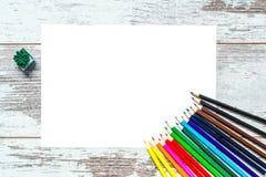 Lápis coloridos coloridos, uma folha do Livro Branco em um fundo de madeira do vintage, placas vestidas de madeira com quebras Fotografia de Stock Royalty Free