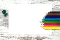 Lápis coloridos coloridos, uma folha do Livro Branco em um fundo de madeira do vintage, placas vestidas de madeira com quebras Fotografia de Stock