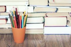 Lápis coloridos com a pilha de fundo do conceito da educação do livro foto de stock