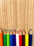Lápis coloridos de madeira com apontar aparas, na tabela de madeira Imagem de Stock