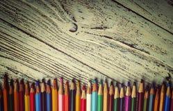 Lápis coloridos em seguido no fundo de madeira Fotografia de Stock