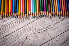 Lápis coloridos em seguido no fundo de madeira Imagem de Stock