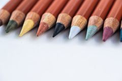 Lápis coloridos em um fundo pastel a um ponto com espaço para o texto imagens de stock royalty free