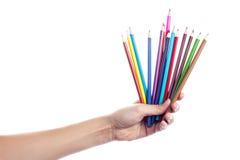 Lápis coloridos em uma mão fêmea em um fundo branco Fotografia de Stock Royalty Free