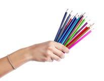 Lápis coloridos em uma mão fêmea em um fundo branco Fotos de Stock Royalty Free