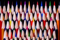 Lápis coloridos empilhados ordenadamente em um teste padrão aleatório da cor mas dentro Foto de Stock